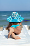 Little girl on the beach relaxing on a deck chair
