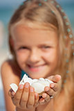 Happy little girl holding seashells - closeup