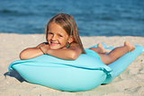 Little girl with inflatable mattress or raft on the beach