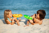 Kids having fun with water pistols on the beach