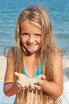 Little girl on the beach playing with sand