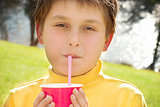 Young boy drinking strawberry milk outdoors