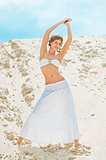 beautiful girl in a white skirt posing on a sand dune