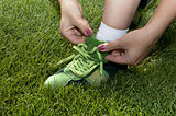 woman ties laces on green shoes