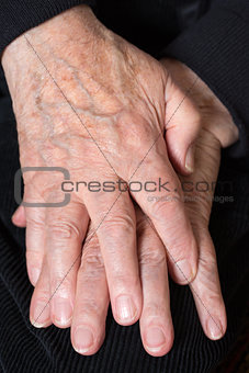 Crossed hands of an old senior
