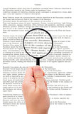 Hand holding magnifying glass reading document
