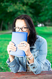 Beautiful young woman with book in park
