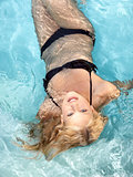 active young blonde woman in a blue pool