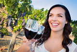 Young Woman Enjoying Glass of Wine in Vineyard With Friends