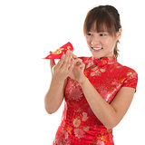 Chinese cheongsam girl peeking into red packets