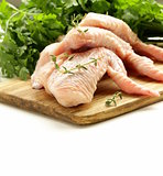 Raw chicken wings on chopping board with herbs