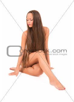 Beautiful young woman with long hair posing nude in studio