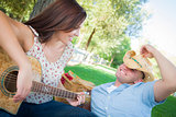 Mixed Race Couple with Guitar and Cowboy Hat in Park