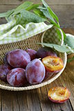 ripe purple plums on a wooden table