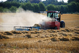 Tractor baling straw in a field