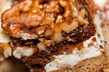 Walnut toffee cake with white cream close up