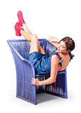 Happy woman in denim dress kicking back on chair