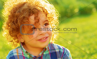 Cute baby boy on green field