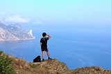 Young traveler looks at the beautiful seascape from the mountain