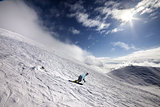 Snowboarder on off-piste ski slope and blue sky with sun