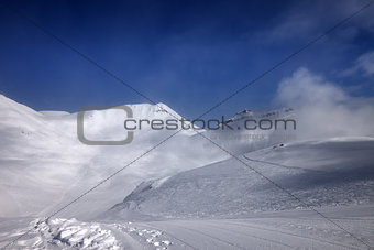 Ski slope with snowmobile trail in nice day