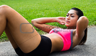 Fit young woman doing sit-ups outdoors