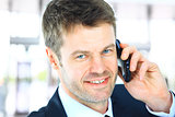 Smiling man using an office phone