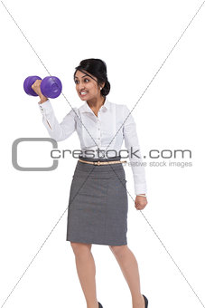 Angry Asian businesswoman holding a dumbbell
