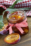 Plum jam in  jar on  wooden table