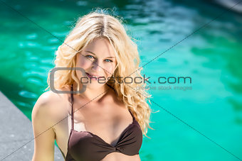 Happy blond girl lying on pool