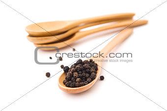 Black pepper on wood spoon