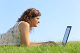 Profile of a beautiful woman lying on the grass browsing a laptop