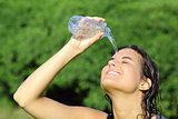 Attractive woman throwing herself water from a bottle