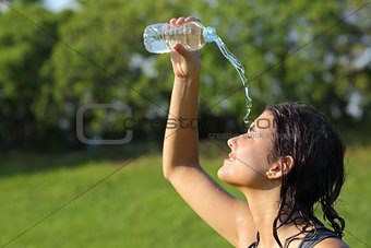 Beautiful woman throwing herself water from a bottle