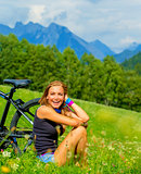 Cheerful female with bicycle on green field