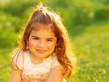 Cute little girl on green field