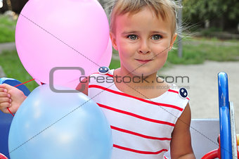 adorable little girl playing with balloons