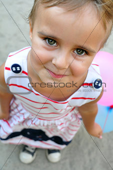 adorable little girl playing with balloons looking up