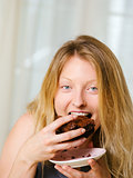 Blond woman biting a chocolate brownie