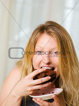 Blond woman biting a chocolate brownie