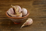 garlic in bowl on a wooden background
