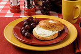 Bagel with cream cheese and grapes