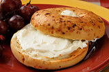 Onion bagel with cream cheese and grapes