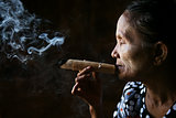 Old wrinkled Asian woman smoking