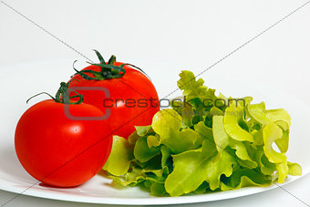 Tomatoes and lettuce on a white plate