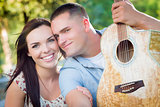 Mixed Race Couple Portrait with Guitar in Park