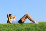 Pretty woman doing crunches on the green grass