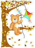 Teddy bear sitting on the tree with kite wind