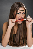 Playful woman biting makeup brush