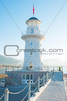 Landscape with a lighthouse in the harbor town of Alanya at dawn.